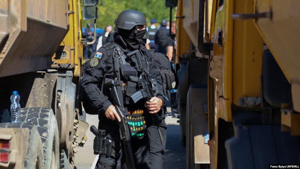Një pjesëtar i Policisë së Kosovës duke patrulluar mes kamionëve, në Jarinjë. (26 shtator)