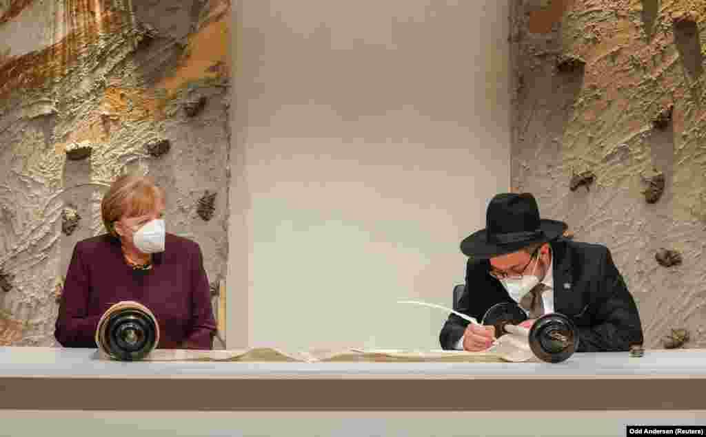 Angela Merkel német kancellár is részt vett a megemlékezésen. Ezen a fényképen azt figyeli, amint Saul Nekrich rabbi beleír a történelmiSulzbachi Tóratekercsbe. Az idei németországi megemlékezés központi eseménye a sok vihart megélt tóratekercs helyreállításának utolsó mozzanata, a munka lezárása az utolsó betűk szertartásos megírása.