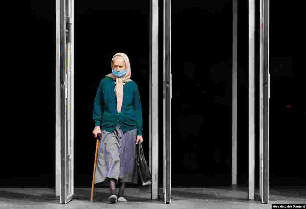 An elderly woman wearing a protective face mask exits a subway station in Kyiv. (Reuters/Gleb Garanich)