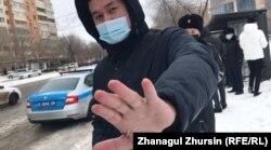 Мужчина в темной одежде и в маске препятствовал корреспонденту Азаттыка освещать акцию протеста. Актобе, 28 февраля 2021 года.