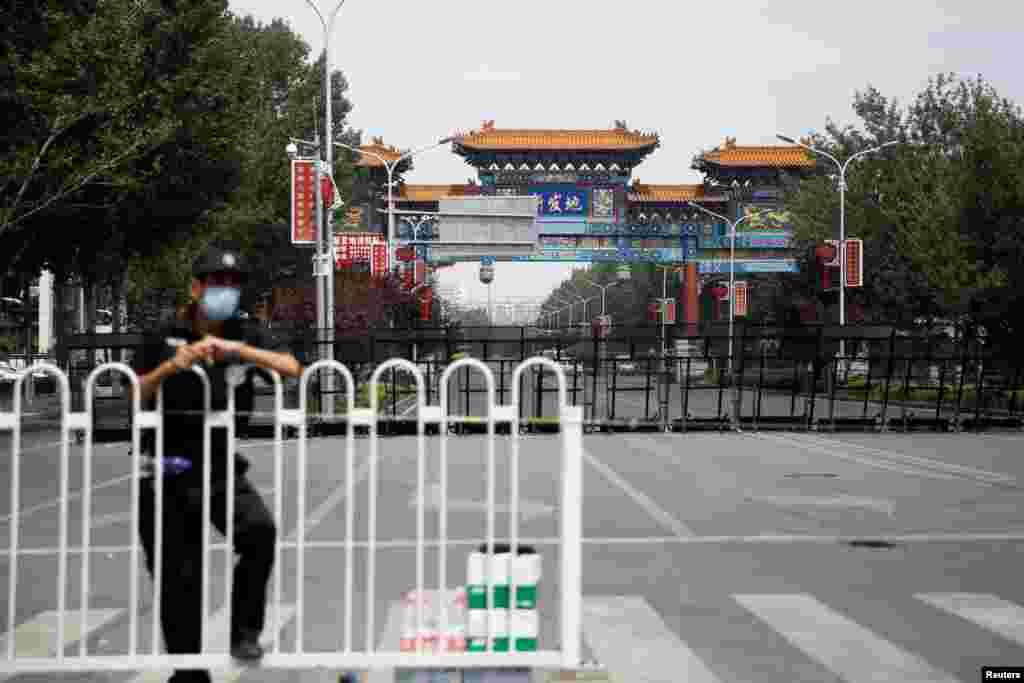 Співробітник служби безпеки в захисній масці біля заблокованого входу на гуртовий ринок Ксінфаді, який був закритий після нового спалаху коронавірусу (COVID-19), в Пекіні, Китай
