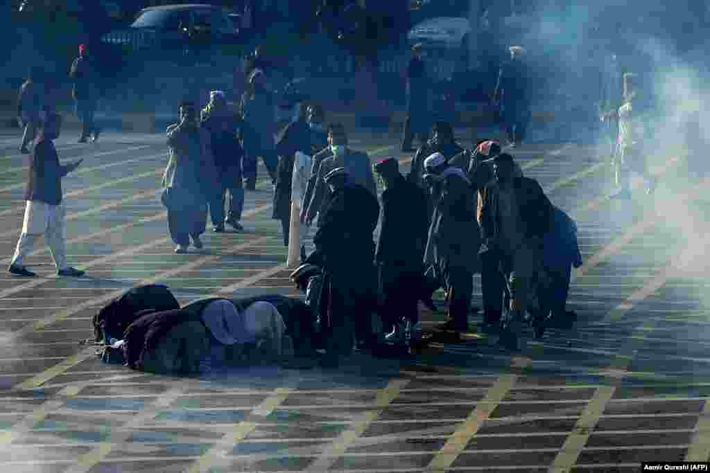 Pakistani government workers pray on a street amid teargas fired by police as they march toward parliament during a protest to demand higher wages in Islamabad on February 10. (AFP/Aamir Qureshi)