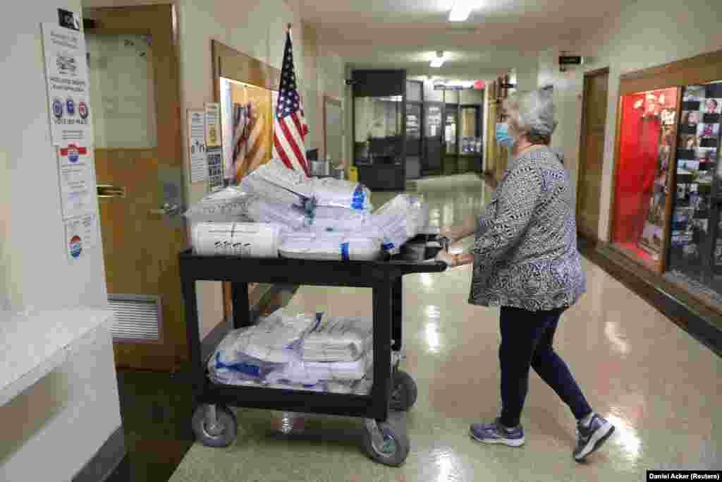 Працівниця виборчої служби штовхає візок із заповненими бюлетенями прямого голосування у муніципальному будинку Кеноша, штат Вісконсін