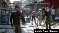 Police officers put up barriers as they guard a street sealed after authorities reimposed lockdowns in selected areas in an effort to stop the spread of the coronavirus disease in the eastern city of Lahore on June 17.