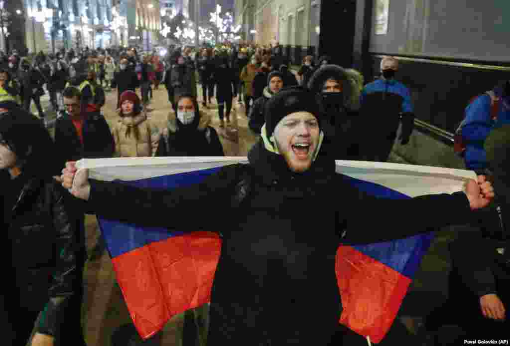 A man drapes a Russian flag across his back as he marches through Moscow in support of Navalny.
