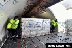 A Sinopharm kínai gyógyszergyártó cég koronavírus elleni vakcináit pakolják ki a Külgazdasági és Külügyminisztérium által vásárolt Airbus 330 típusú teherszállító repülőgépből a Liszt Ferenc-repülőtéren 2021. február 16-án.