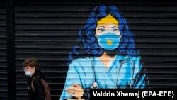 Egy maszkot viselő fiú sétál el egy kórházi nővért ábrázoló graffiti előtt Pristinában, 2020. december 3.