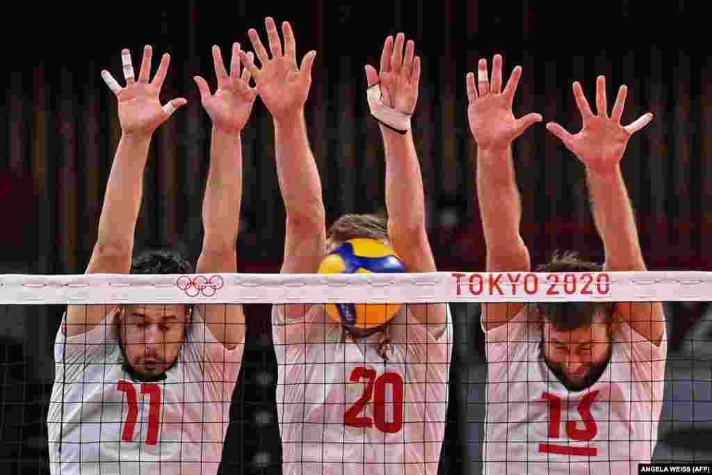 (Зліва направо) Поляки Фабіан Джизга, Матеуш Бенієк та Міхал Кубяк намагаються заблокувати м'яч у попередньому волейбольному турнірі для чоловіків із командою Венесуели. Токіо, 28 липня 2021 року