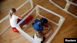 Djeca se igraju u jaslicama tokom demonstracije za upotrebe štitnika od širenja korona virusa. Fotografija je zabilježena u njemačkom gradu Velbertu, 8. april 2021.