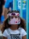 Alegra Bajrami (levo), sa maskom u cilju zaštite od korona virusa, ulazi u školsko dvorište prvi dan nove školske godine u glavnom gradu Kosova Prištini. Škole na Kosovu otvorene su 14. septembra po prvi put od marta kada je kriza zbog pandemije počela.
