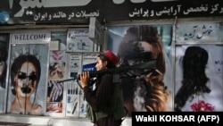 Egy tálib harcos sétál el egy szépségszalon mellett, amelynek kirakatában a nők képeit festékkel fújták le Kabulban, 2021. augusztus 18-án