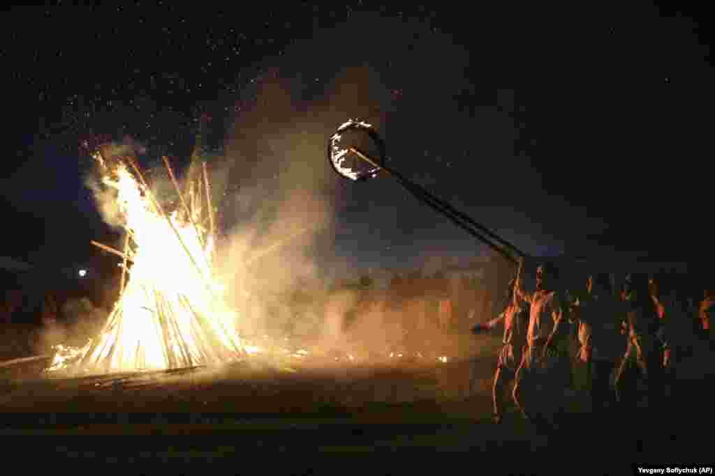 Villagers walk around a bonfire celebrating the summer solstice in Okunevo, some 200 kilometers northeast of Omsk in Siberia.