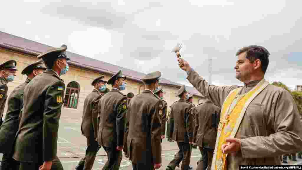 Священник окроплює святою водою курсантів