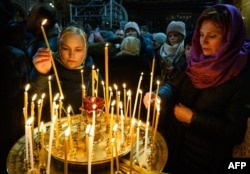 People light candles during Christmas midnight Mass at Moscow's Cathedral of Christ the Savior on January 6.