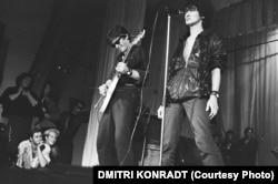 Viktor Coj (jobb oldalon) és a Kino fellépése 1987-ben a Leningrádi Rock Klubban, miközben őket nézi a helyi zenei élet két kulcsfigurája, Joanna Stingray és Borisz Grebenscsikov (balra lent). Coj lett az orosz popzene történetének egyik legikonikusabb alakja. Autóbalesetben vesztette életét 1990-ben, de azóta is legendaként él tovább a volt Szovjetunió utódállamaiban. A nyugati fiatalok is hallották a zenéjét – még ha nem is tudnak róla. A Grand Theft Auto videójátékban szóló fiktív Vladivostok FM rádió egyik száma a Kino klasszikus dala a Gruppa Krovji (Vércsoport). A számot a licenc lejárta után, 2018-ban kivették a játékból.