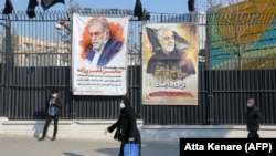 IRAN -- Iranians walk past a poster depicting late Revolutionary Guards commander Qasem Soleimani (R) and nuclear scientist Mohsen Fakhrizadeh, assassinated last month, in the capital Tehran, December 30, 2020