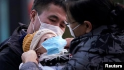 Родители надевают ребенку медицинскую маску у входа на вокзал в Шанхае