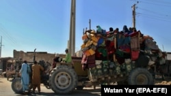 Afghans flee their villages after fighting intensified between Taliban militants and security forces in Lashkar Gah on October 12.
