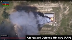 A video grab allegedly shows smoke billowing from what was said to be destroyed Armenian military equipment on the Azerbaijani-Armenian border on July 15.