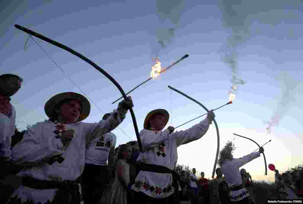 People in ethnic costumes shoot arrows during Ivana-Kupala celebrations.
