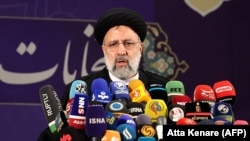 Iranian judiciary chief Ebrahim Raisi speaks to reporters after registering his candidacy for Iran's presidential election at the Interior Ministry in Tehran on May 15.