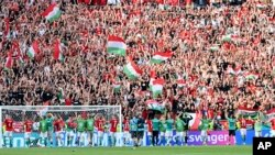 Hungary's players celebrate with fans after the Euro championship Group F match with France at Ferenc Puskas stadium in Budapest on June 19.