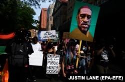 Protestuesit në SHBA mbajnë në duar portreti e George Floyd si dhe mbishkrime të tjera kundër racizmit.