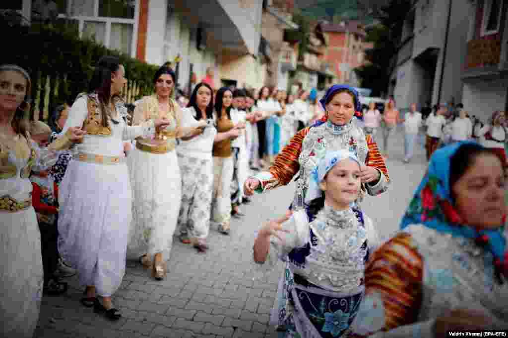 Местные женщины в национальных костюмах танцуют на улицах деревни
