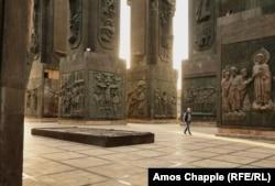 Мужчина проходит через колонны памятника «Хроника Грузии».