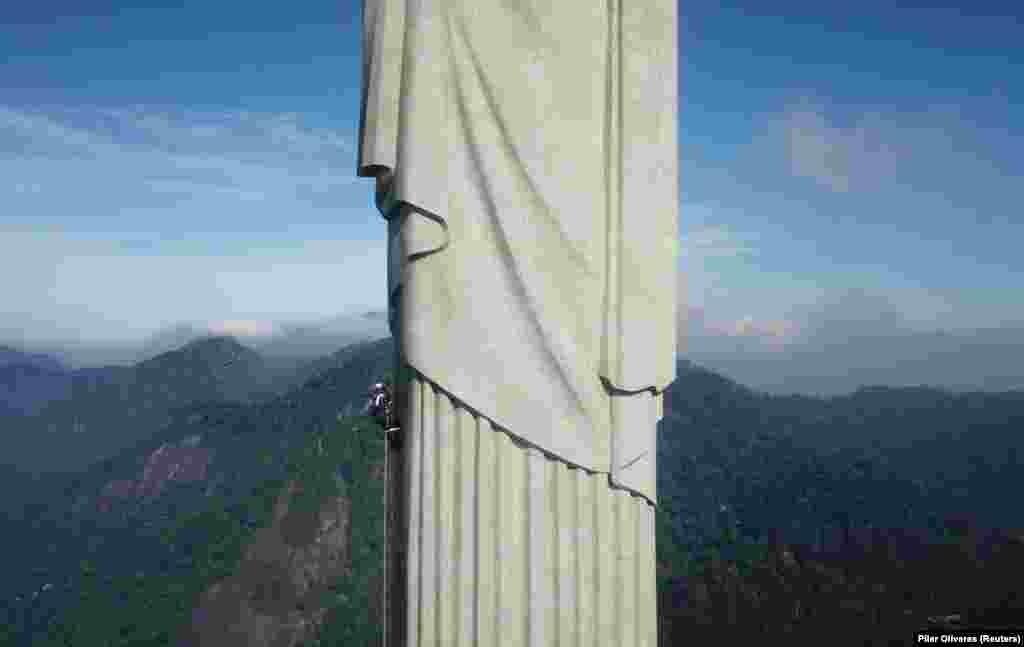 Munkások másznak fel a szobron.