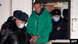 Aleksei Navalny is escorted out of a police station on January 18 in Khimki, outside Moscow.