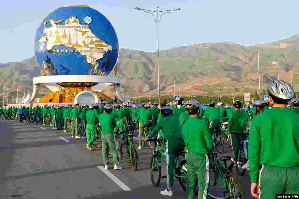 Cyclists stand in front of a 30-meter monument in Ashgabat honoring cycling, which has become an important component of state propaganda in Turkmenistan that promotes a healthy lifestyle. Thousands of tracksuit-wearing officials were brought along for a ride on June 3 as President Gurbanguly Berdymukhammedov spearheaded a parade to mark World Bicycle Day. (AFP/Igor Sasin)