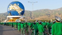 Cyclists gather in front of a 30-meter monument to cycling, which has become an important component of state propaganda promoting a healthy lifestyle, in Ashgabat in June 2020.