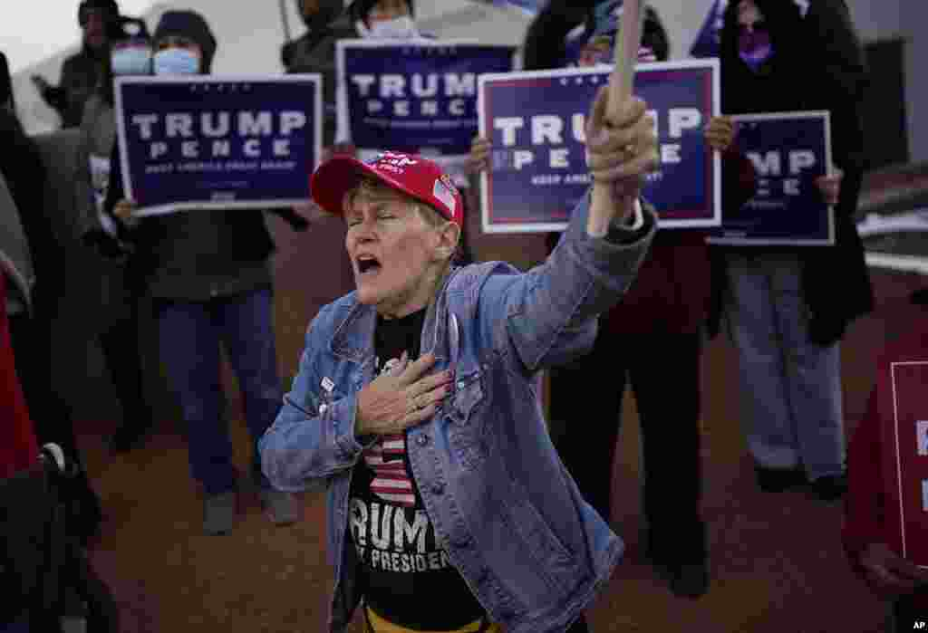A supporter of President Donald Trump holds her hand over her heart during a protest of the election outside of the Clark County Election Department, Sunday, Nov. 8, 2020, in North Las Vegas.