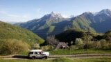 A vehicle carrying health-care workers and a Red Cross volunteer drive to a mountain village in the remote Kolasin region of central Montenegro.