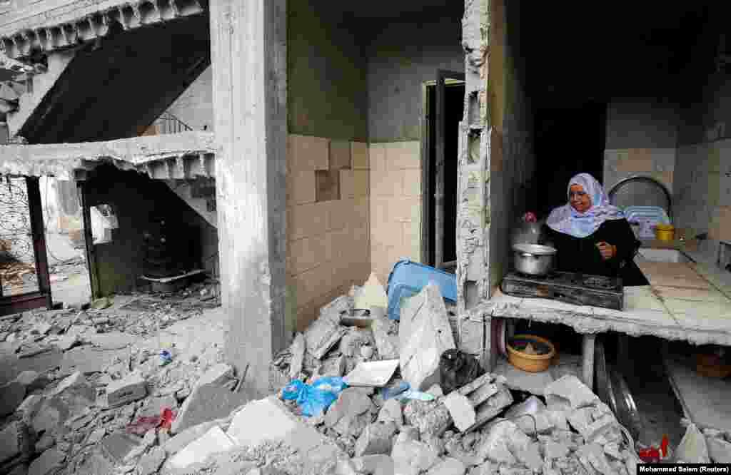 Палестинская женщина готовит среди обломков своего дома, который был разрушен во время израильско-палестинских боев в Секторе Газа, 23 мая 2021 года