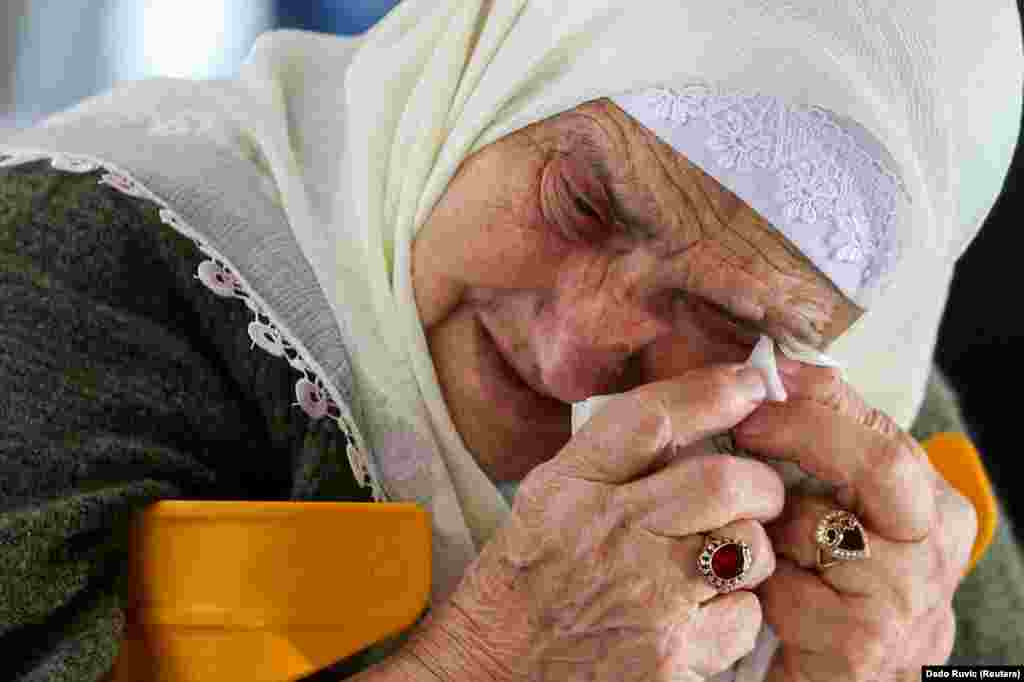 Боснийская мусульманка в Мемориальном центре геноцида Сребреница-Потокари ожидает приговора в апелляции бывшему сербскому военному деятелю Ратко Младичу за преступления во время боснийской войны