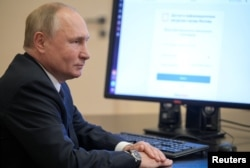 Russian President Vladimir Putin votes online at his residence outside Moscow.
