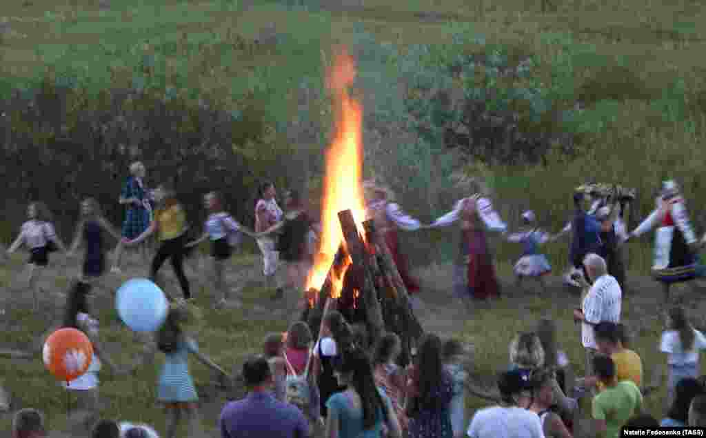 People dance around a bonfire.