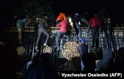 Protesters attempt to break through the gates of the White House -- the building that houses parliament and the president's office -- during a rally against the results of a parliamentary vote in Bishkek on October 5.