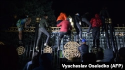 Протестующие пытаются прорваться через ограждение здания правительства во время митинга против результатов парламентских выборов в Кыргызстане. Бишкек, 5 октября 2020 года.