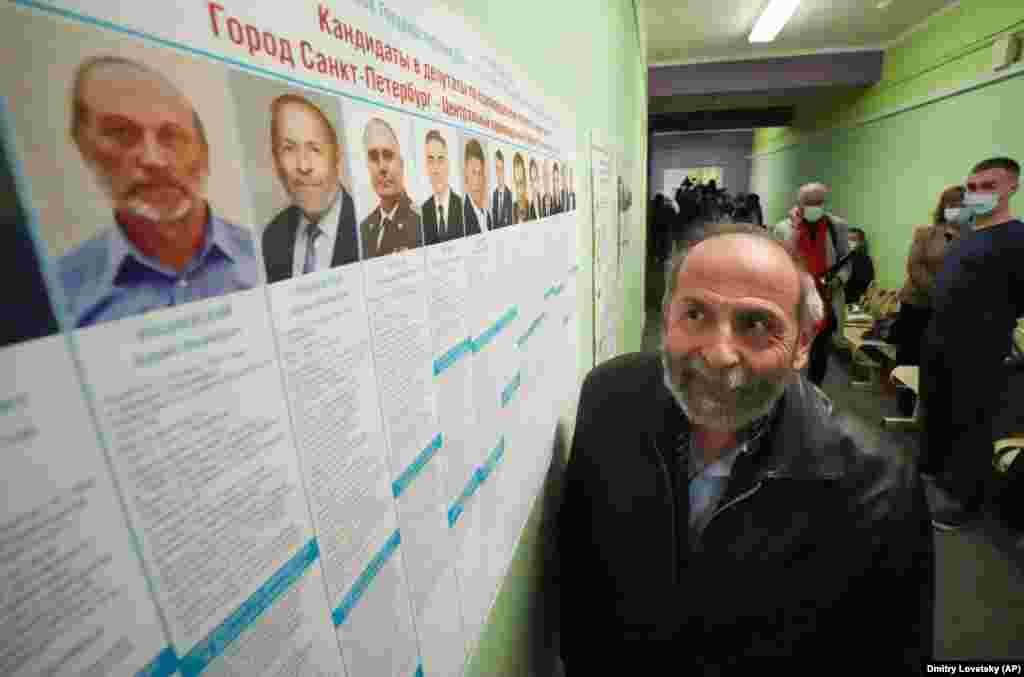 Boris Vishnevsky of the Yabloko party, who is running for both the State Duma and the regional legislature, looks at a list of candidates at a polling station in St. Petersburg on September 19. Vishnevsky faced rival candidates who not only had the same name, but even looked like him.