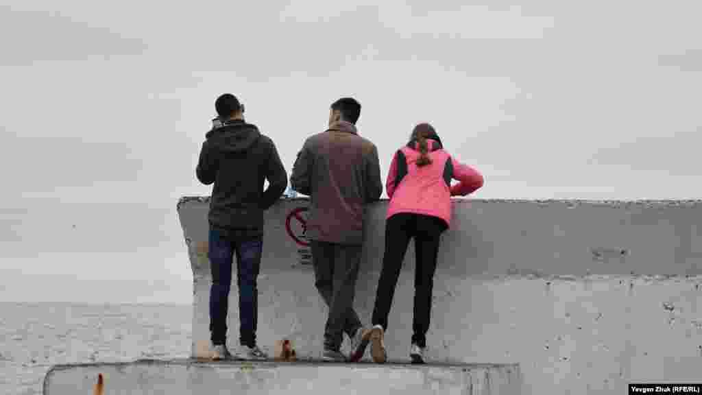 Молоді люди дивляться на воду з буни