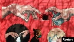 Женщина на фоне граффити на коронавирусную тему в Мумбаи.