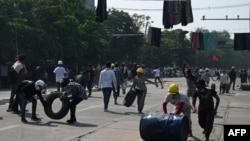 معترضان در میانمار در حال ساخت مانع مقابل نظامیانی که برای سرکوب تظاهرات در خیابانها حضور دارند