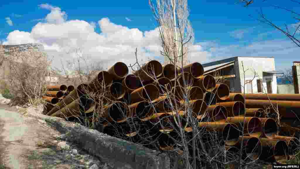 Поруч складена гора залізних труб великого діаметра