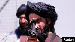 Një militant taliban drejton armën në drejtim të aparatit fotografik jasht aeroportit të Kabulit.