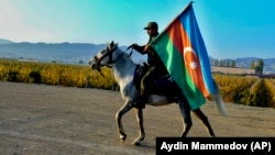An Azerbaijani soldier with a national flag rides a horse in Ganca, Azerbaijan's second-largest city, near the border with Armenia, on November 10.