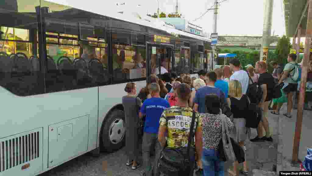 На вході в автобус люди товпляться, не дотримуючись соціальної дистанції