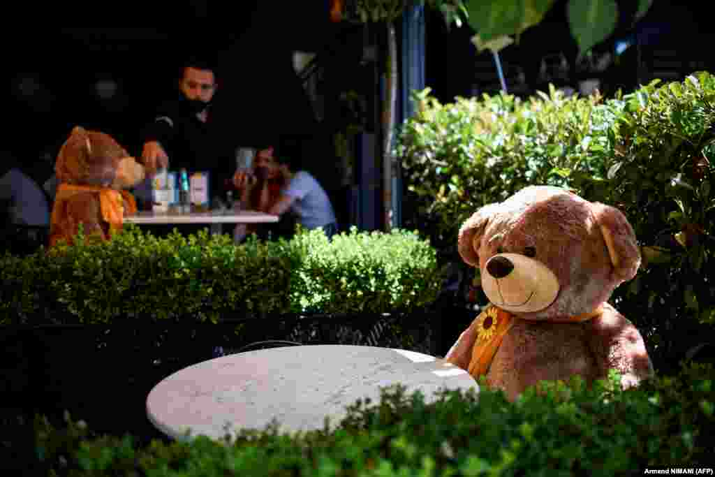 A large teddy bear, used to enforce social distancing, is pictured sitting at a cafe in Pristina as Kosovar authorities announced new measures to fight against a resurgence of the coronavirus. (AFP/Armend Nimani)